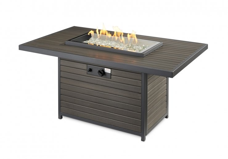 A dark grey colored rectangular fire table with flames on, over clear glass beads.