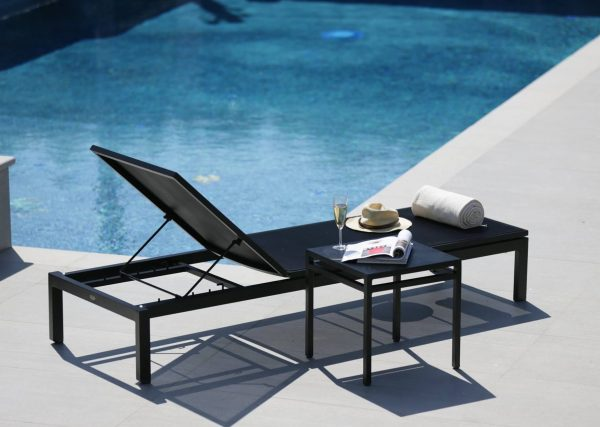 The Toscana lounger side table next to the lounger in black beside a pool.