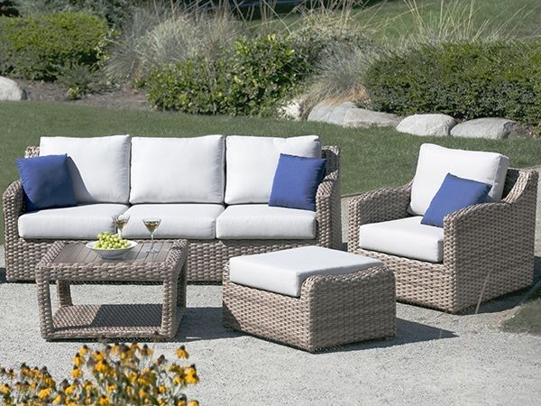 The Auckland Bay patio furniture collection, with cream cushions, blue pillows and grassy background.