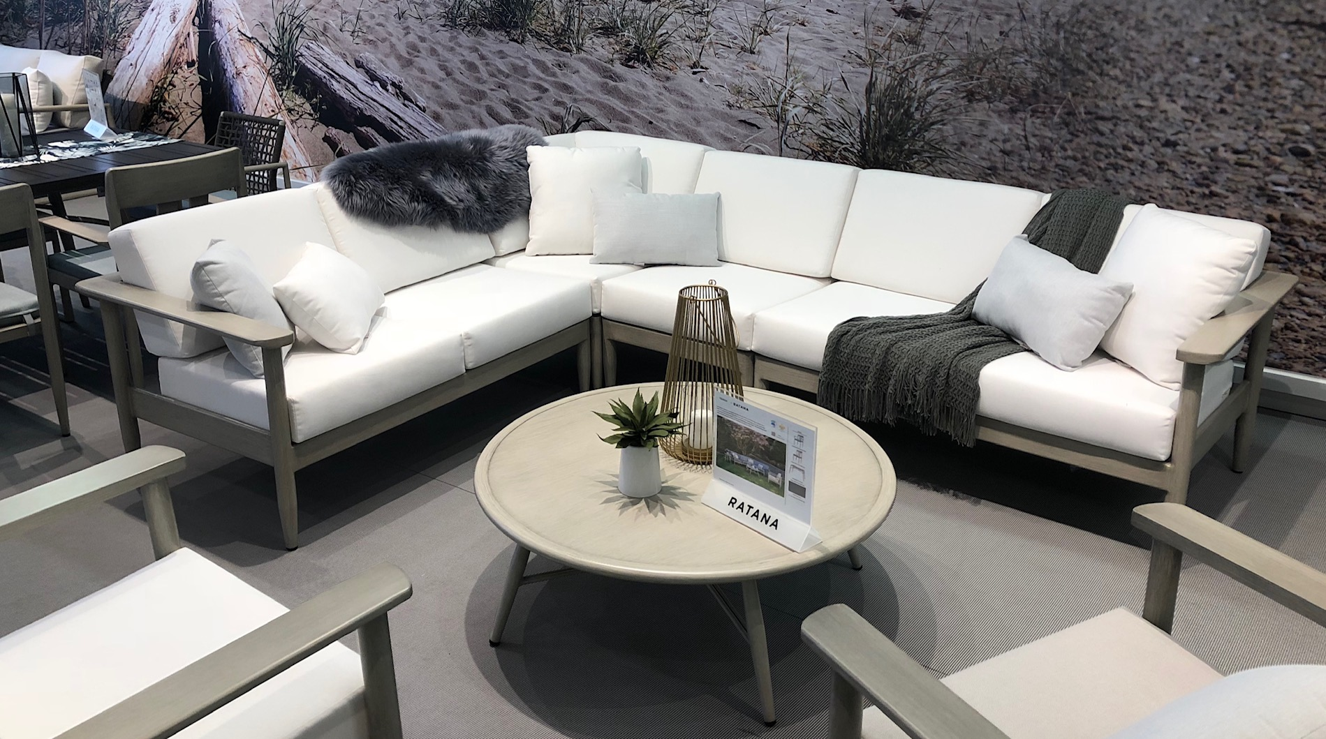 The Polanco sectional by Ratana with a round coffee table and blankets over the cushions.