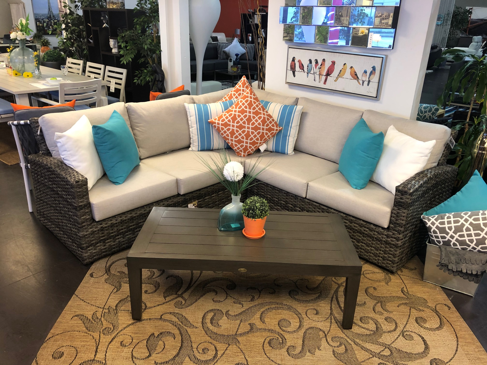 Grey wicker patio sectional with bright toss pillows & metal coffee table.