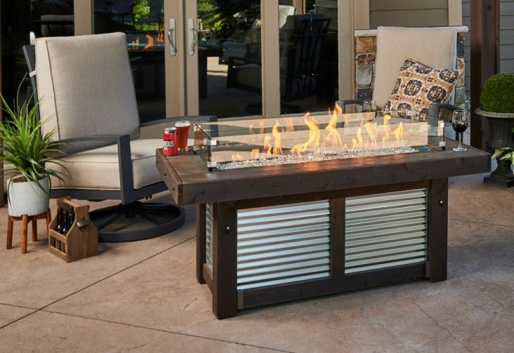 The Denali Brew fire table with flames on and patio set in back ground.