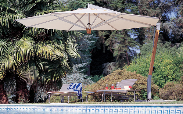 A cream color Fim P20 Patio Umbrella overhanging 2 lounge chairs outdoors with bushes behind them.