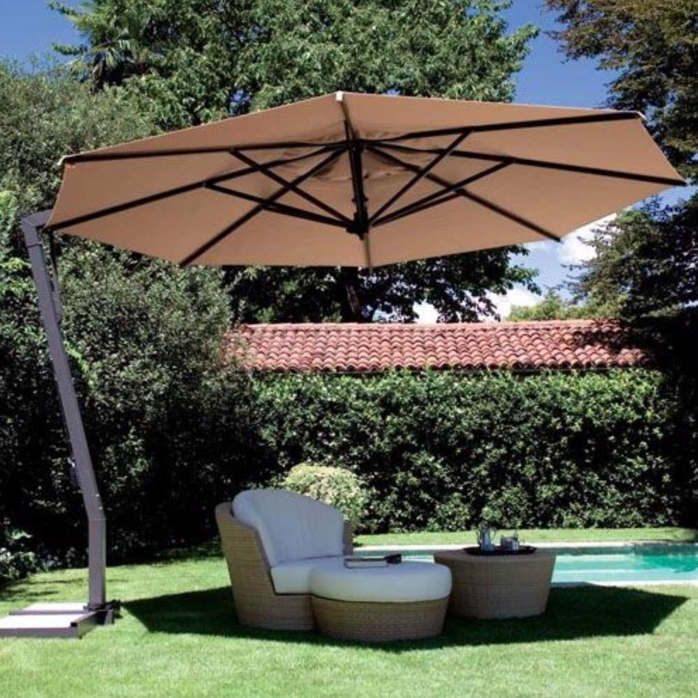 The Fim P20 Patio umbrella is shading a chair on the lawn.