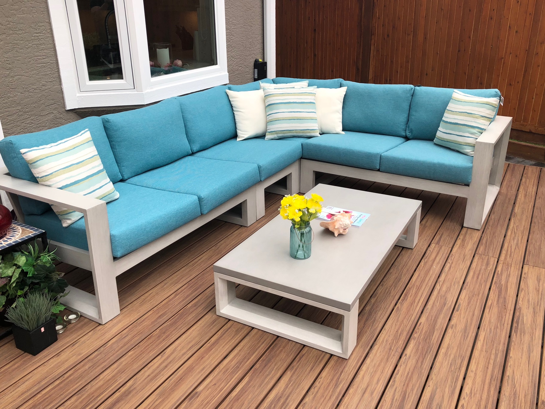 A white metal frame with blue cushions Element patio sectional with coffee table on a wood deck.