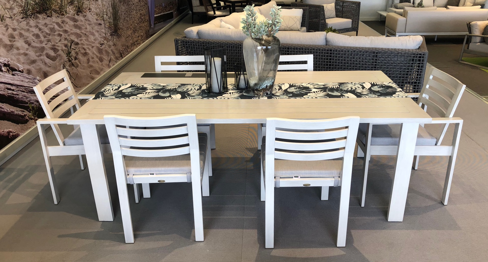 The Element Dining Table with 6 chairs in a white metal frame and grey cushions.