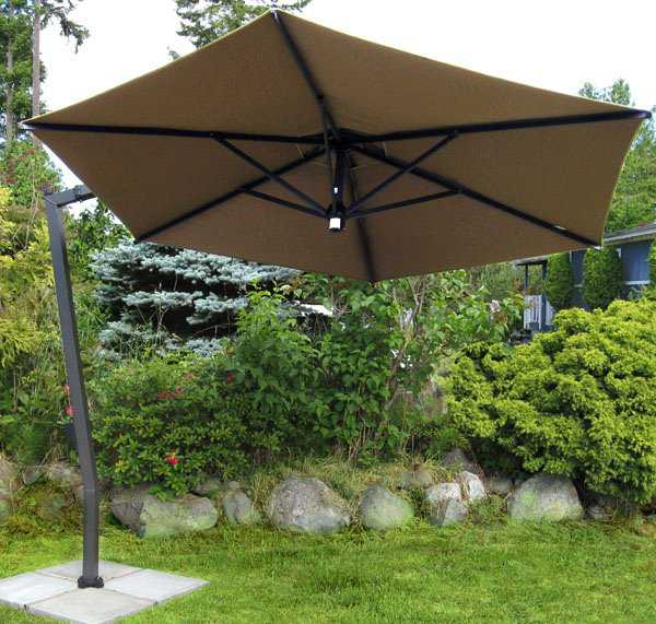 A large tan colored offset umbrella sits on grass with bushes in the background.
