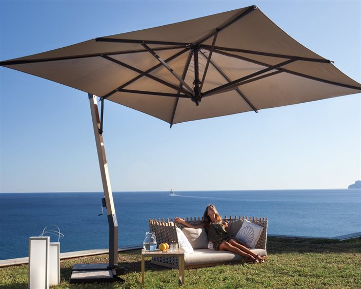 A woman lounges on a patio sofa by the ocean, covered by a brown patio umbrella with green grass.