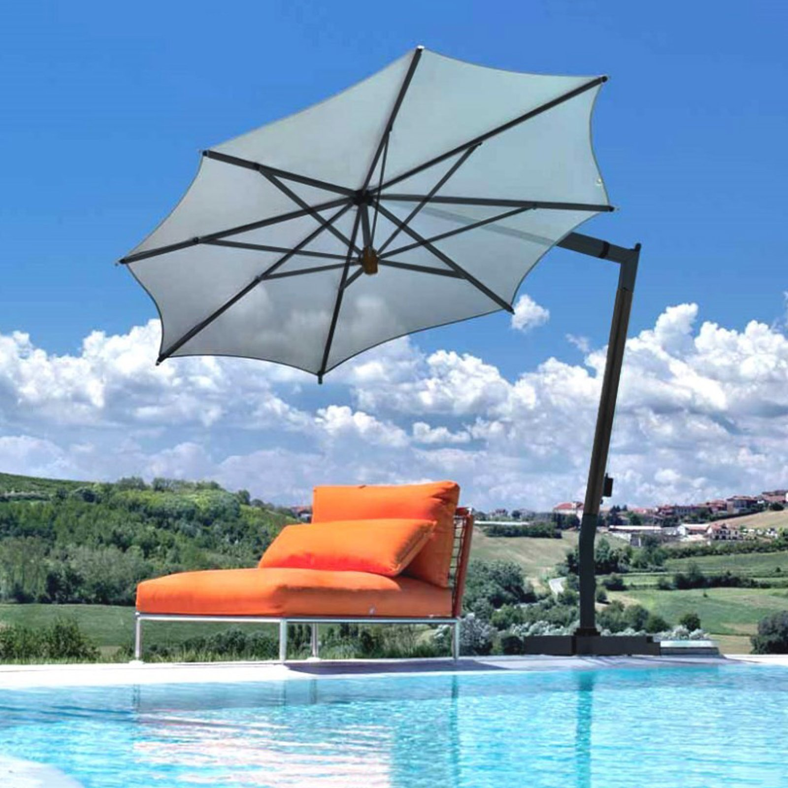 An orange lounge chair next to a pool, is shaded by a large beige Fim patio umbrella in the Italian countryside.