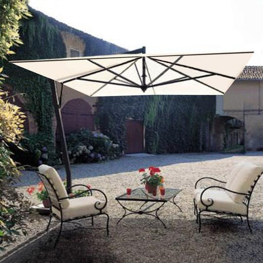A cream colored square shaped Fim patio umbrella sits over top 2 metal patio chairs in an outdoor garden.