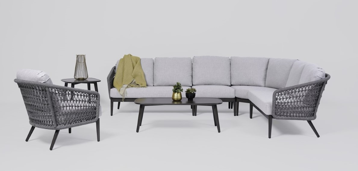 The Poinciana sectional by Ratana with coffee table, chair and yellow blanket.