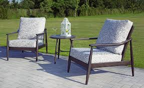 2 Bolano club chairs with side table, on patio with green grass in background.