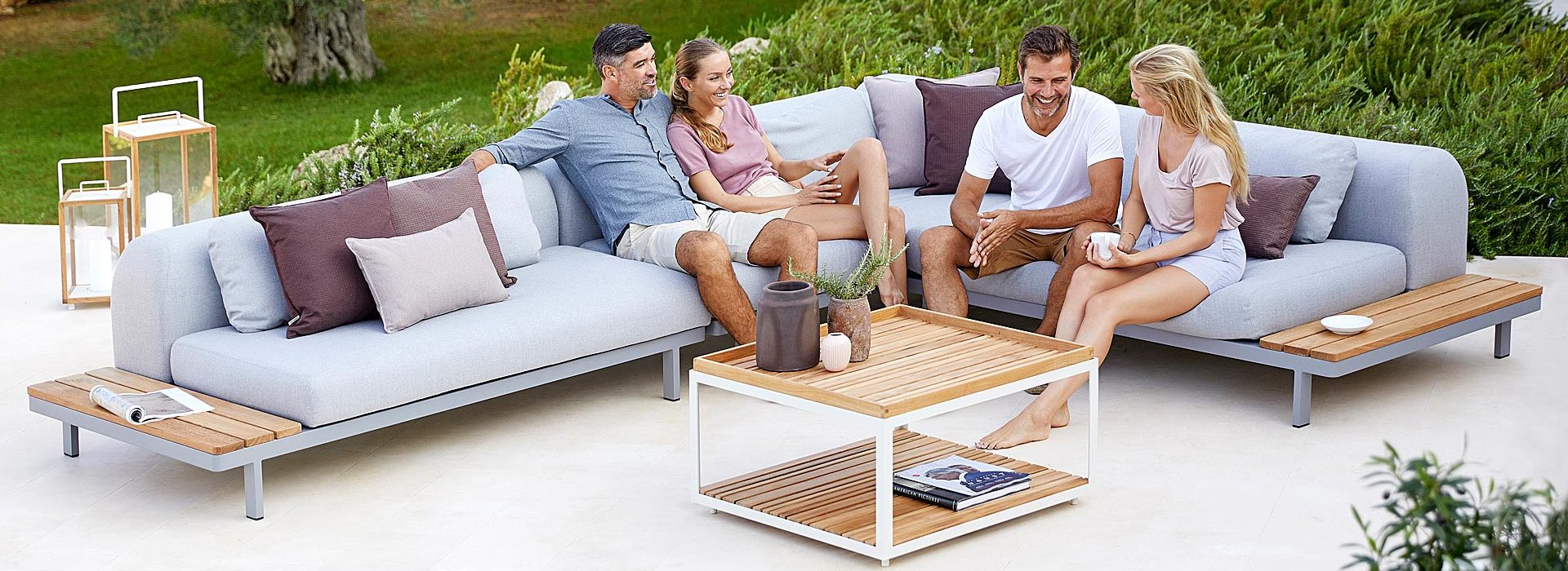 Two couples sitting on patio furniture, grass in background and patio lamps.
