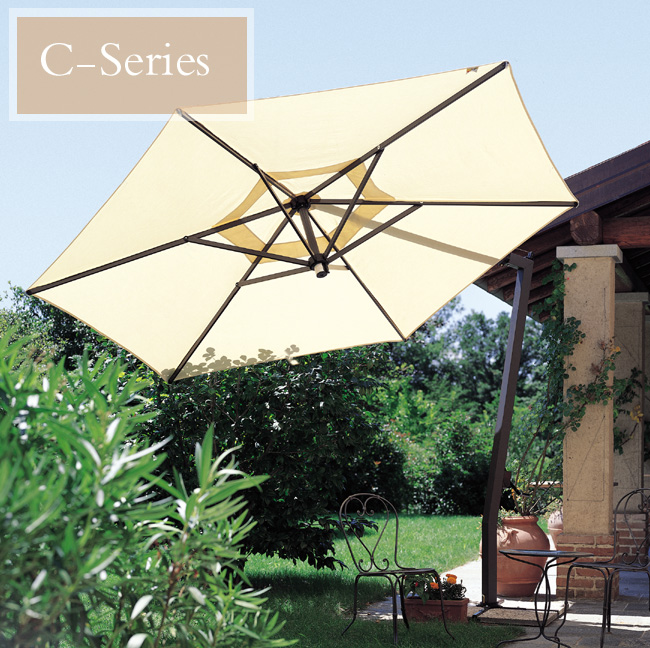 A cream color offset patio umbrella tilted side ways outdoors, with green bushes and trees around it.