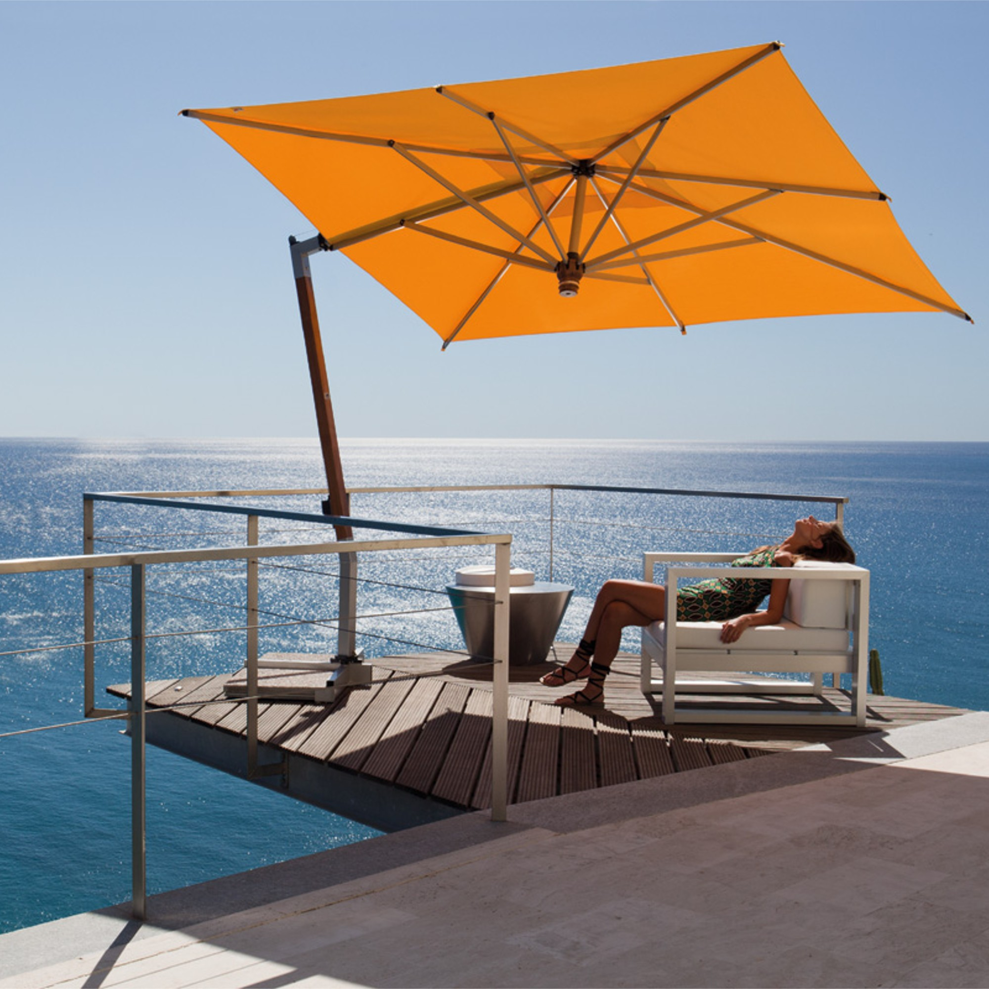 A woman sits back in a chair on her patio under a yellow Cantilever Umbrella overlooking the ocean.