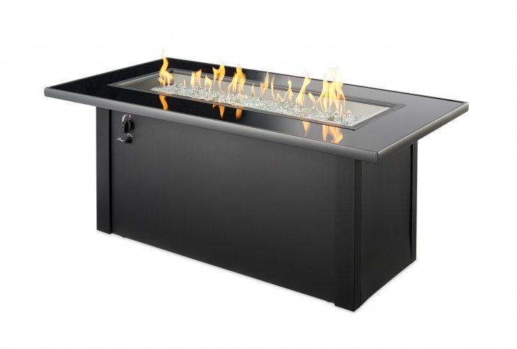 A black base rectangle fire table with shiny black glass top, gas flames burning over clear glass beads.
