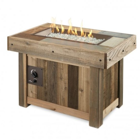 A rectangular fire table in a vintage wood color with gas flames burning over clear fire glass.