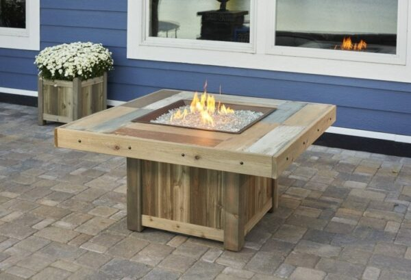 The Vintage square fire table with flames on, blue house in back ground.