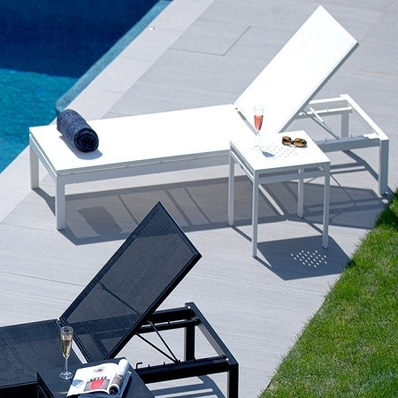 A white & black mesh lounger next to a pool, white side table, black towel rolled up.