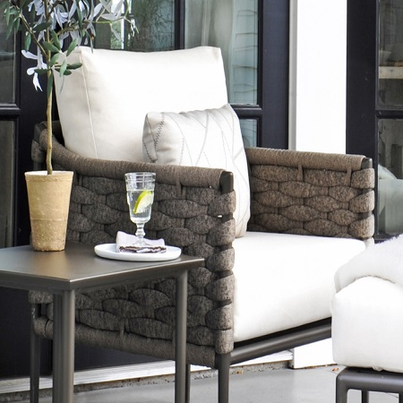 Bogota club chair, outside next to a side table with plant & glass of wine.