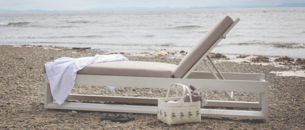 white frame patio lounger on a rocky beach, ocean in background, basket in front
