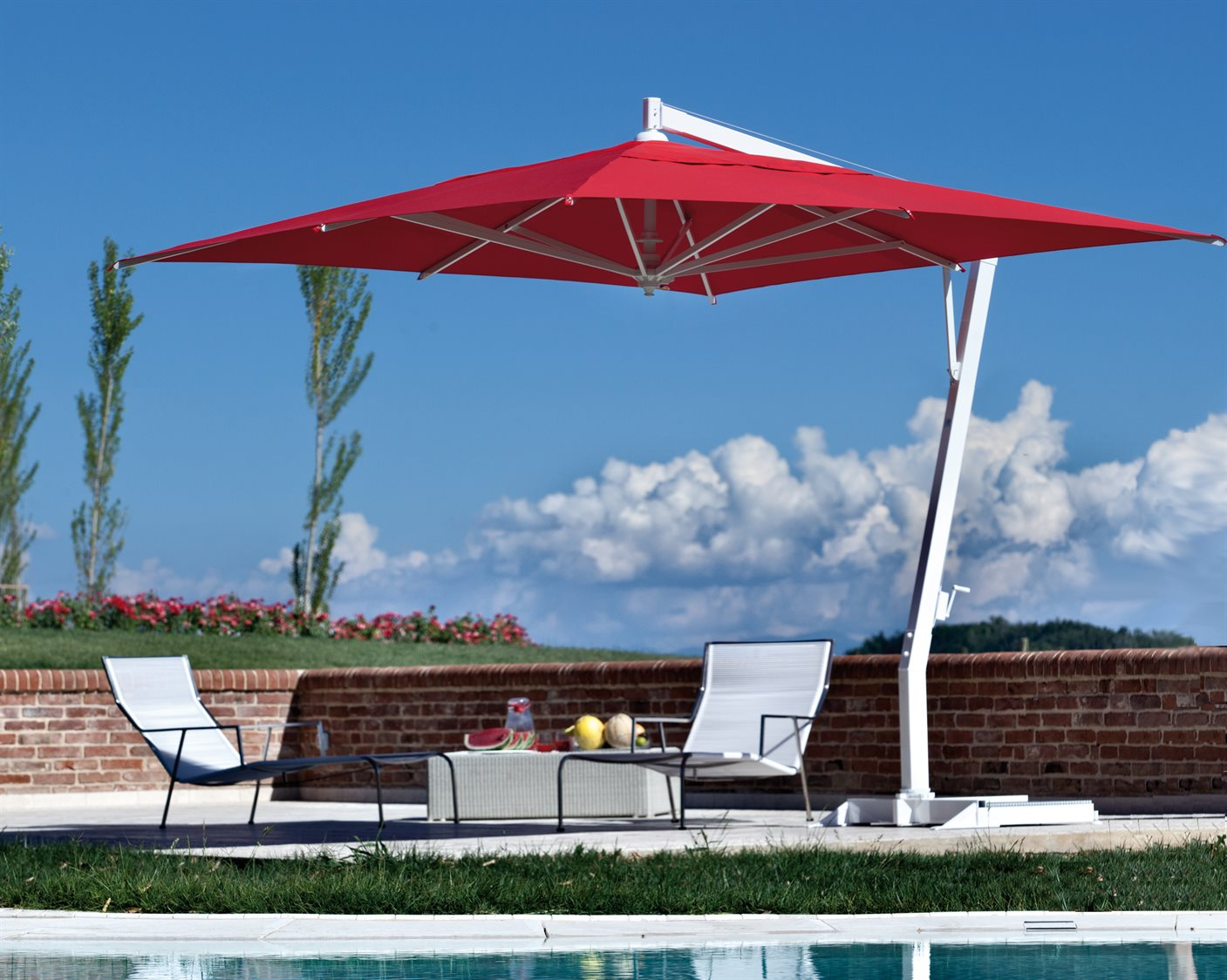 A red Fim Umbrella with a silver pole, covers 2 white lounge chairs with blue skies and a brick wall in the background.
