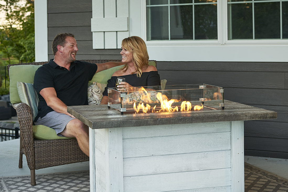 A couple sitting on their patio set with a gas fire table going.