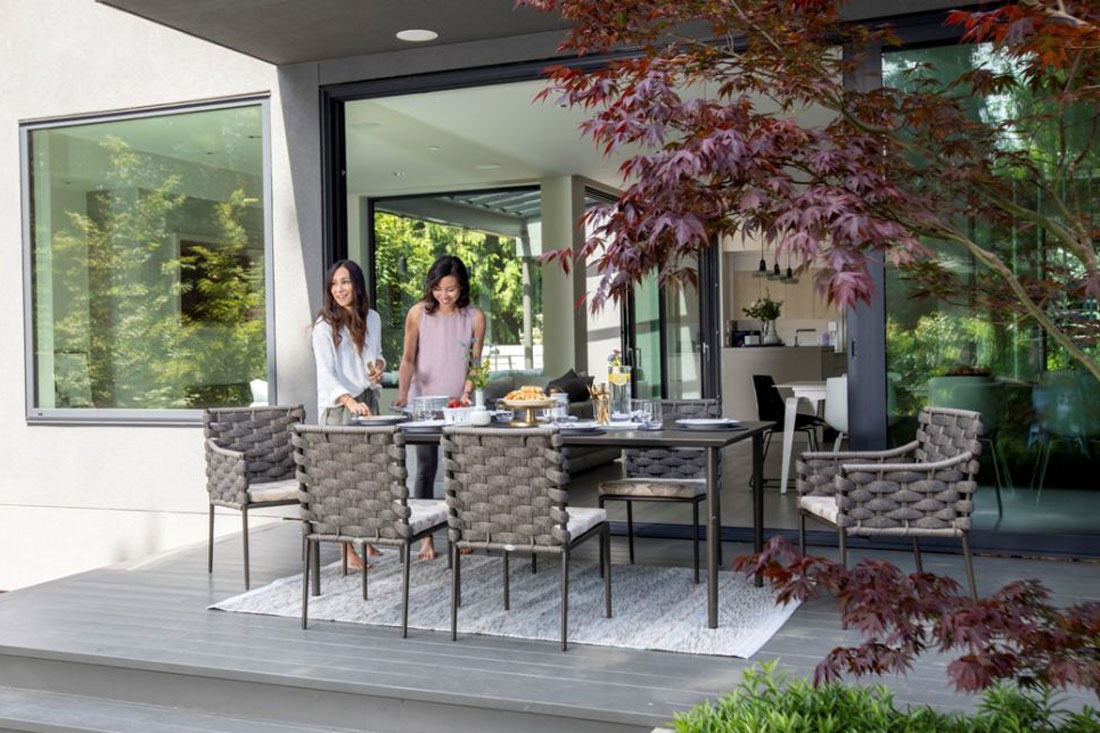 Two women smiling and getting ready for lunch on their patio set.