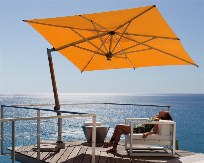 Lady sitting on outdoor furniture under a yellow umbrella by the ocean.