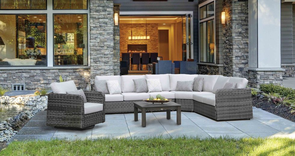 A sectional and club chair in grey wicker on a patio furniture Winnipeg