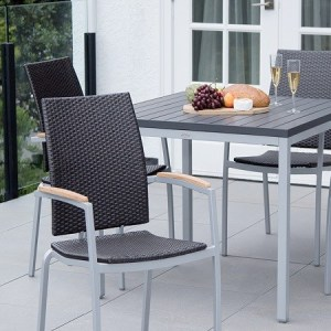 4 patio dining chairs with a square dining table outside on a patio.