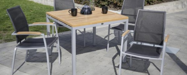 4 black mesh chairs around a teak wood patio table with tea setting.
