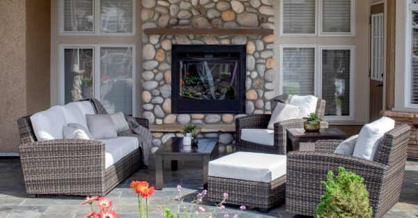 The Coral Gables love seat on a back patio, with 2 club chairs and stone fire place in background.