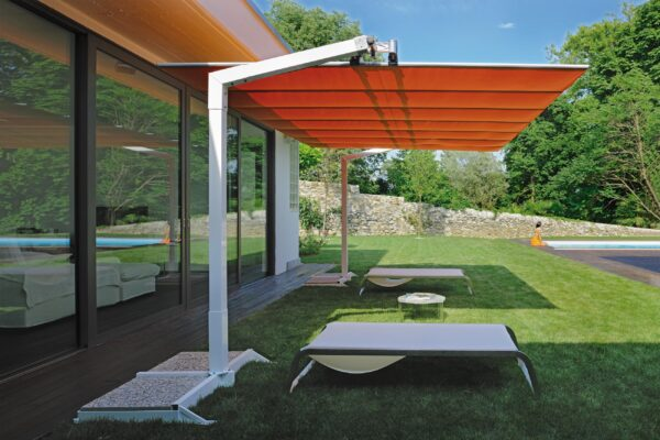 a residential Fim Flexy shade system in orange canopy over loungers and grass.