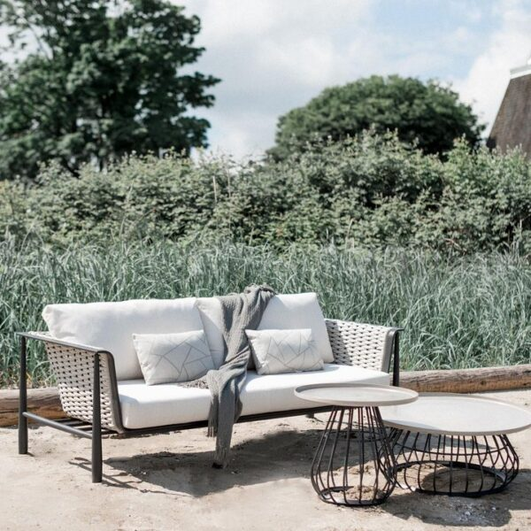 The Diva sofa Ratana with 2 round tables in front, cream colored cushions and green trees in the background.