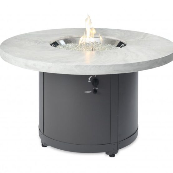 The white onyx Beacon fire table with flames on.