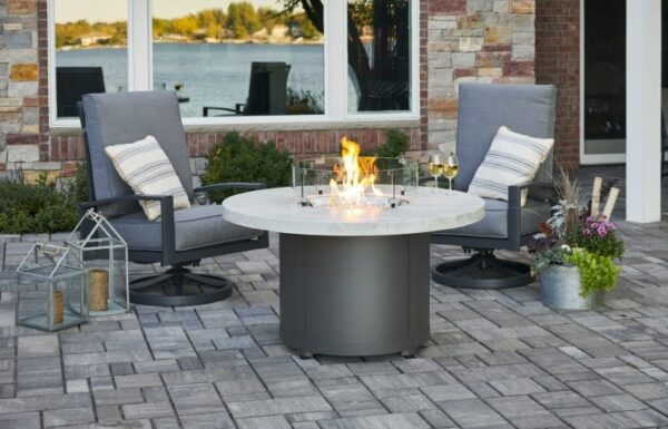 The white onyx beacon fire table with wine glasses and 2 chairs around it.