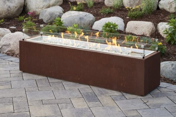 The Cortlin fire table with flames on and glass wind guard.