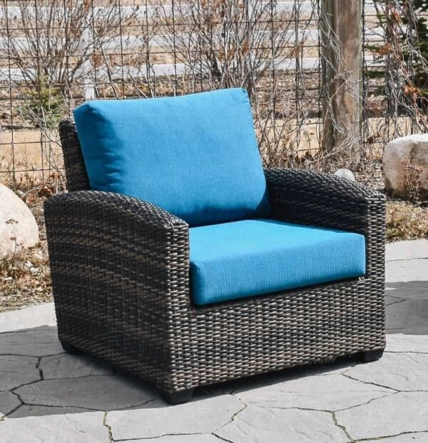 The Coral Gables club chair with blue cushions on a stone deck with fence in background.
