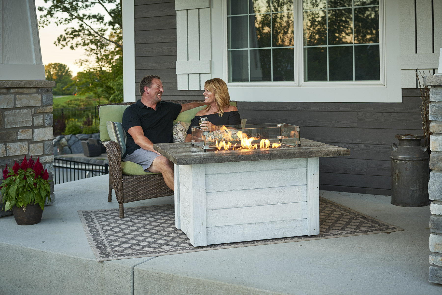 A couple sitting on their outdoor furniture with gas fire tables in Calgary and the flame is on.