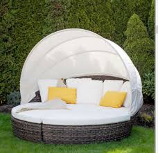 The Coral Gables cabana daybed bed on grass with 2 yellow toss pillows.